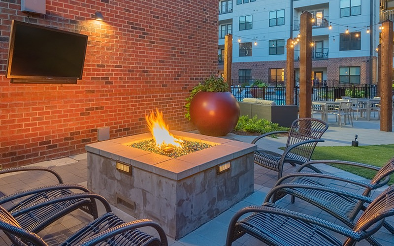 firepit with lounge chairs all around near a mounted TV